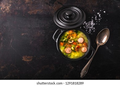 stew with fresh vegetables and sausages on a dark background