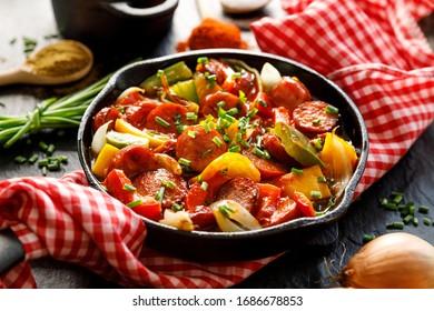 Ragoût de poivrons et saucisses sur fond noir, en poêle en fer forgé, gros plan. Plat hongrois traditionnel appelé lecho