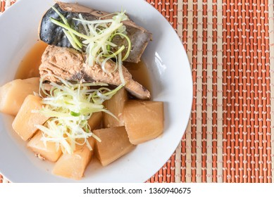 Stew simmered home yellowtail with radish in a plate on a bamboo napkin copy space - Japanese dish fish