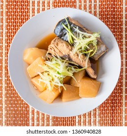 Stew simmered home yellowtail with radish in a plate on a bamboo napkin close up - Japanese and Chinese fish dish