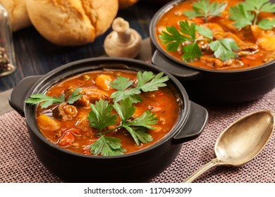 Stew soup with meat, potatoes, mushrooms and red pepper in bowl