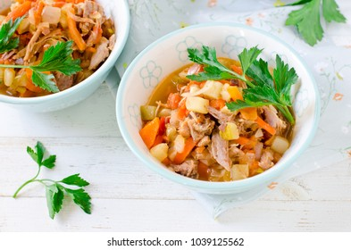 Stew of turkey and vegetables (zucchini, onions, carrots, tomatoes, bell peppers) on a white wooden table