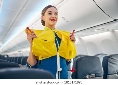 Stewardess in the cabin of the passenger airplane doing training of instruction on safety measures in the event of an emergency before the flight