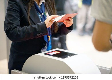 The stewardess checking the documents for boarding the plane at the airport. A female airport employee checks the passport of the passenger. A man in a tourist trip at the airport. Selective focus.