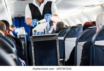 Stewardess cleaning garbage in airplane after lunch.