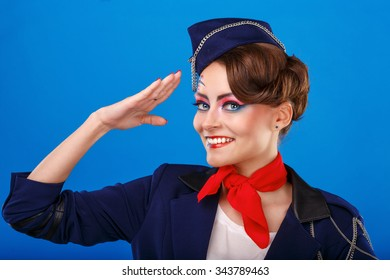 Stewardess with face art salutes. Young attractive girl in a blue suit flight attendants. Air services. Service.