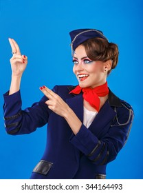 Stewardess with face art shows arms up. Young attractive girl in a blue suit flight attendants. Air services.