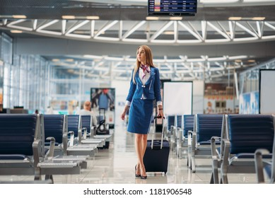 Stewardess with hand luggage going in airport hall