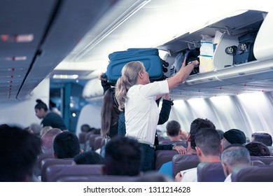 The stewardess helps the passengers to put their luggage in the cabin of the plane. Stewardess in the airplane. Selective focus. August 8, 2018. Amsterdam. Netherlands.