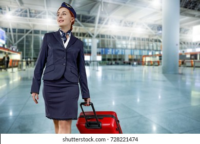 stewardess with red suitcase on airport