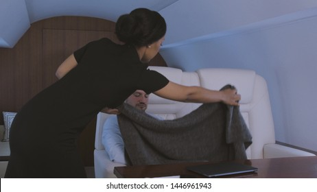 Stewardess taking care of passenger. Flight attendant covering tired sleepy businessman with blanket during trip on private business jet.