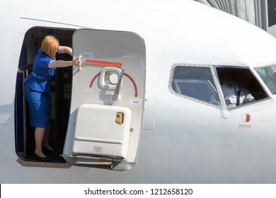 Stewardess tries to close the door on the plane standing on the airport. Aircraft preparation on the airport.