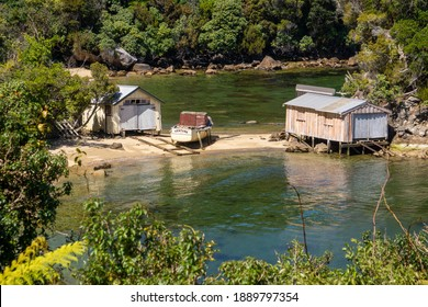 Stewart Island, Southland New Zealand-November 4, 2020: Old boatsheds on the sandy beach and the calm water of beautiful Golden Bay with surrounding bush.