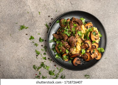 Stewed beef with mushrooms and a side dish of lentils on a black plate. Top view with place for text.