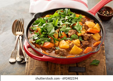 Stewed beef with potatoes, carrot and parsley in a cast iron pan