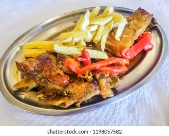 Stewed beef rib with chips and pepper served on metl tray