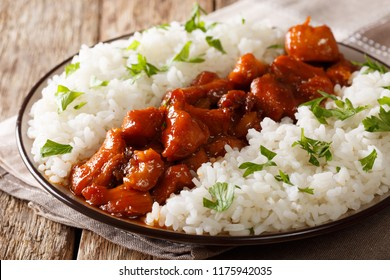 Stewed Bourbon chicken in sauce with whiskey, sugar, ginger and soy, served with rice on a plate on the table. horizontal