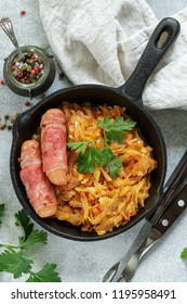 Stewed cabbage with carrots, onions and tomatoes and sausages in bacon with parsley and spices in a cast iron pan. Bigos. Delicious lunch. Selective focus