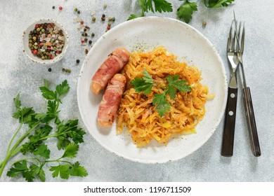 Stewed cabbage with carrots, onions and tomatoes and sausages in bacon with parsley and spices in a white plate. Bigos. Delicious lunch. Selective focus