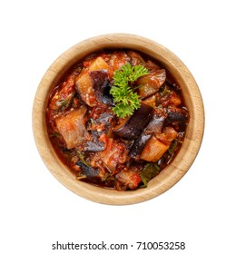 Stewed eggplant with tomatoes and herbs in wooden bowl isolated on white background. Top view.