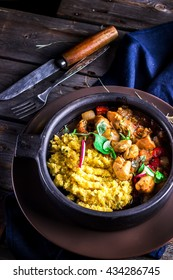 Stewed meat with bright vegetables and couscous in ceramic bowl. Dark wooden background. Selective focus.