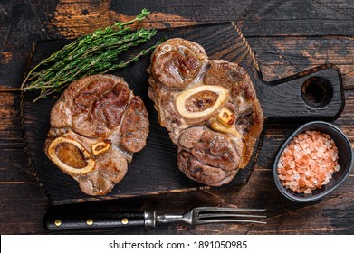 Stewed meat on the bone Osso Buco beef shank, italian ossobuco steak. Dark wooden background. Top view.
