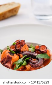 Stewed octopus squid with tomatoe sauce in a plate with bread and water glass