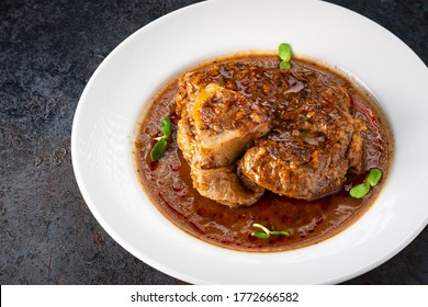 Stewed Osso Buco dish with tomato gravy on a white plate and a stone background, close up