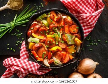 Piment rôti et saucisse avec tomates dans un poêle en fonte sur fond noir, vue de dessus. Le traditionnel ragoût hongrois appelé lecho