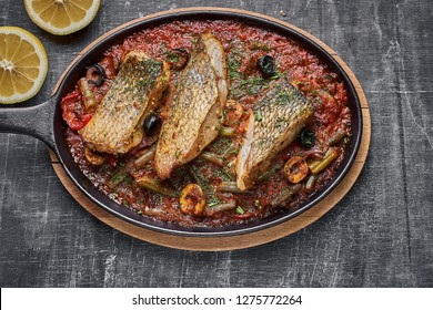 Stewed perch in tomato sauce, serve food in the Provencal style, in a pan. top view , copy Space.