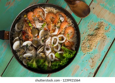 Stewed seafood rice on green wood background