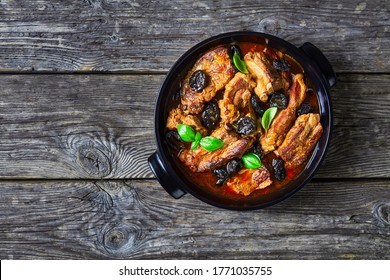Stewed short pork ribs with dried plums or prunes, pork broth, onion, and garlic, decorated with fresh basil, served on a black baking dish on an old barn wood background, copy space