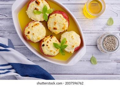 Tomates ragoûtées farcies au fromage sur fond bois. Mise au point sélective.