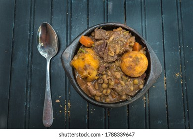 Stewed veal with potatoes, carrots and spices in a clay bowl on a wooden base
