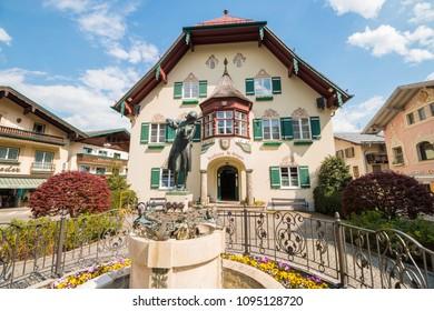 St.Gilgen, Austria - April 23, 2018: Mozartplatz in alpine town St.Gilgen with a statue of Wolfgang Amadeus Mozart as a child in front of Rathaus (Townhall). Popular touristic destination.