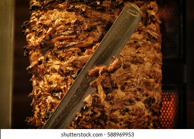 A stick of Arab shwarma in front of the grill, a popular Middle Eastern snack.           Shawarma in the greek restaurant