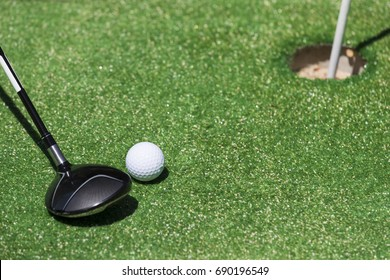 Stick with a ball on an artificial golf course