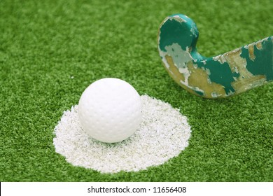 Stick and ball on a green grass