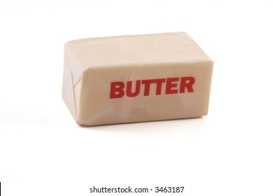 A stick of butter (1/2 cup) photographed from a slight angle above on white background.