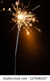 Stick firework lit with orange sparks to celebrate the new year