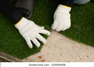 Stick with glue artificial turf grass on floor. Worker install green grass