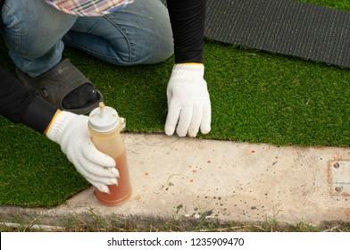 Stick with glue artificial turf grass on floor. Worker install green grass