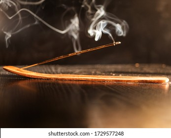 Stick Holder and Incense Stick with Smoke on Black Background. Pure relaxation theme.