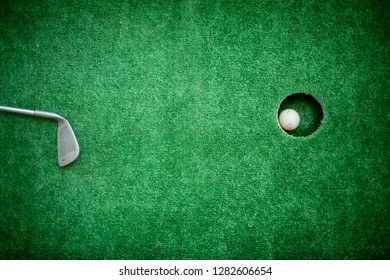 the stick lies on the field next to the hole. stick lying near golf ball. green golf sport. the stick lies to the hole.