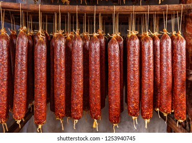 Stick of salami are smoked on the background of the meat factory