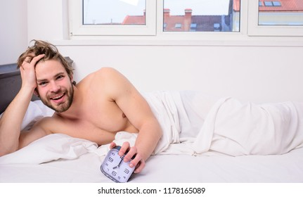 Stick schedule same bedtime wake up time. Enough sleep for him. Regulate your bodys clock. Man unshaven tousled hair wakeful face having rest. Good morning. Man unshaven lay bed hold alarm clock.