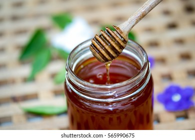 Stick to scoop honey in bottle with wooden background.