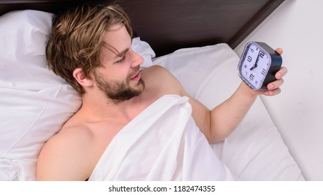 Stick sleep schedule same bedtime and wake up time. Sleep regime habits concept. Man sleepy drowsy unshaven bearded face covered with blanket having rest. Man unshaven lay awake bed hold alarm clock.