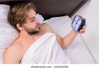 Stick sleep schedule same bedtime and wake up time. Man sleepy drowsy unshaven bearded face covered with blanket having rest. Sleep regime habits concept. Man unshaven lay awake bed hold alarm clock.
