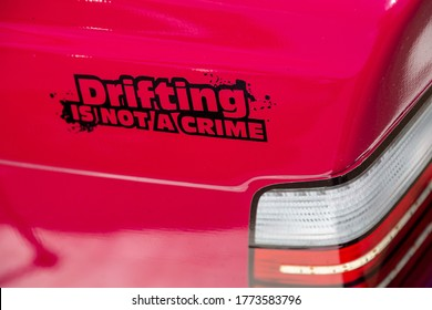 Sticker with the inscription drifting is not a crime on the red body of a sports drift car near the taillight. Close-up. Horizontal orientation.